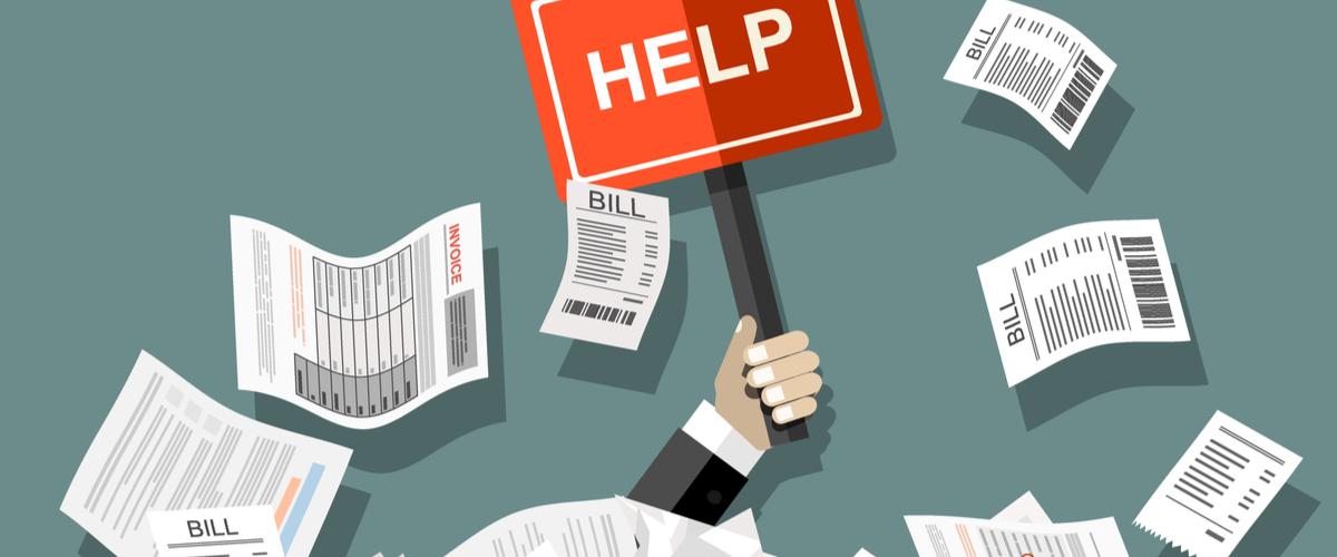 Zakenman die wordt bedolben onder de rekeningen die hij niet kan betalen. HIj houdt een bordje met HELP erop omhoog.