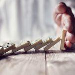 Een hand die vallende domino stenen tegenhoudt en daarmee de val doorbreekt