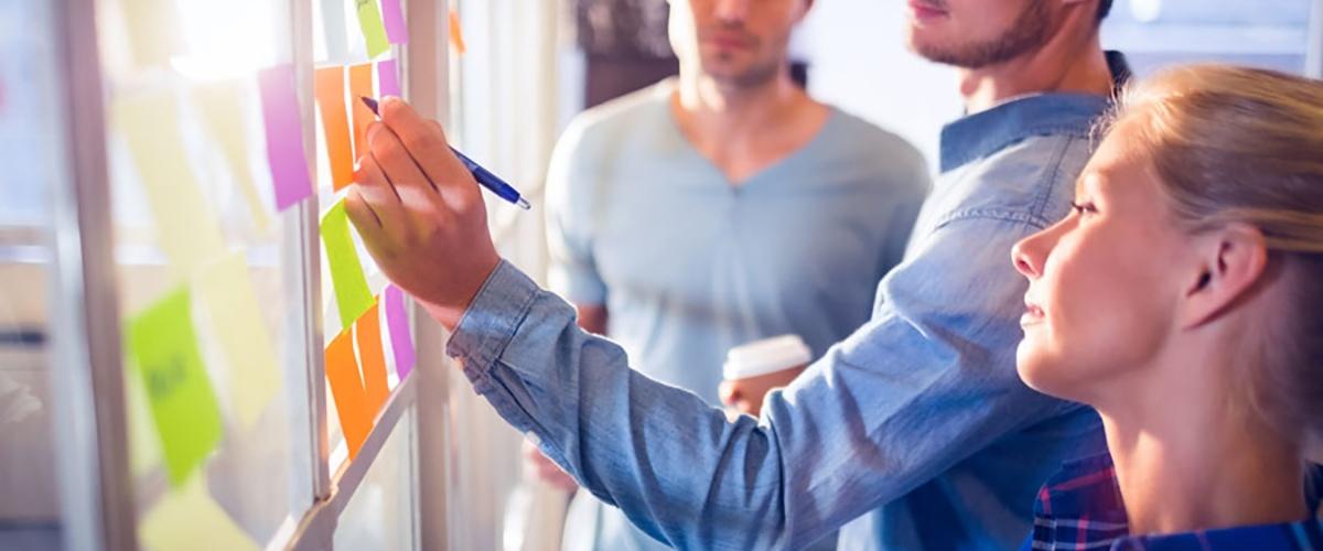 Twee mannen en een vrouw maken met post-its een structuur op een doorzichtig bord