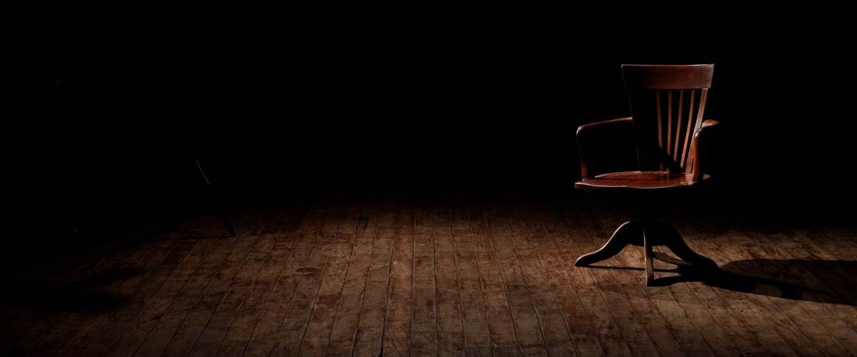Een lege stoel in een donkere ruimte