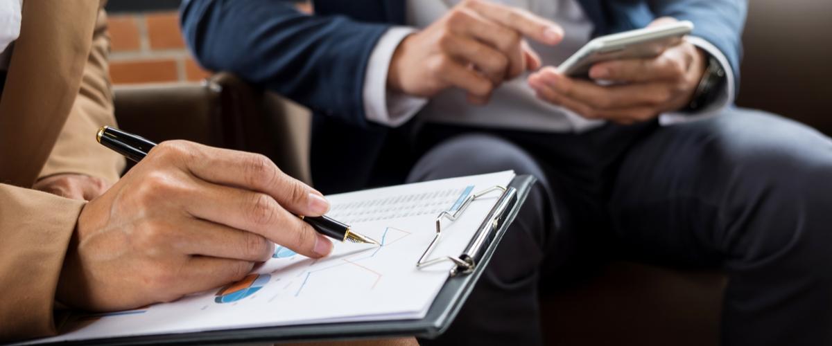 Twee mannen maken notities bij een meeting