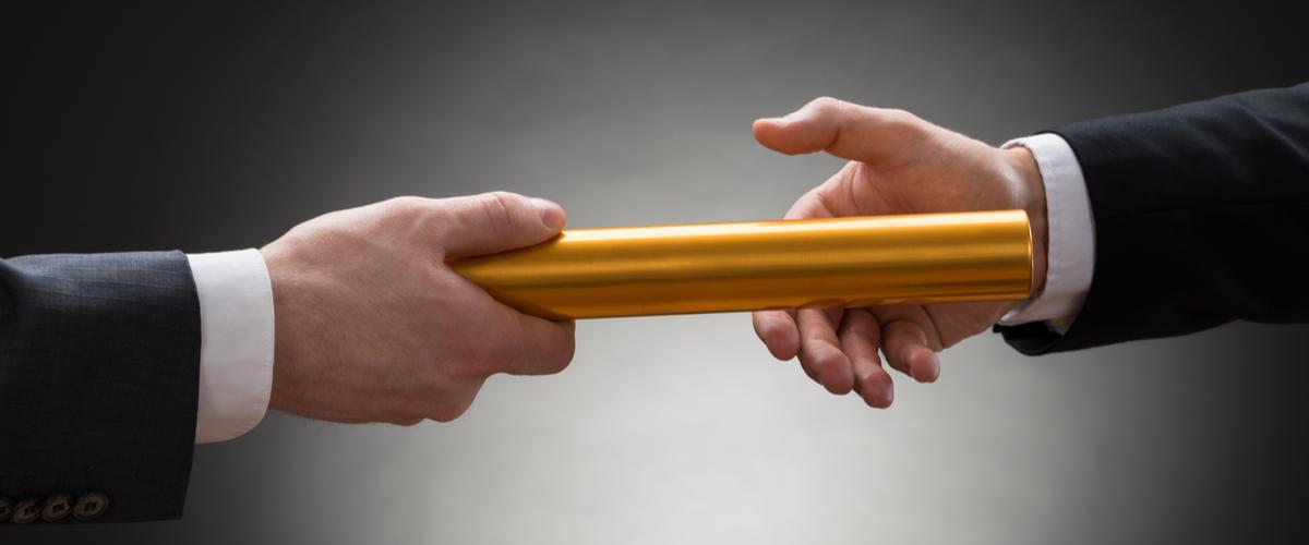 Twee handen die een stokje overdragen