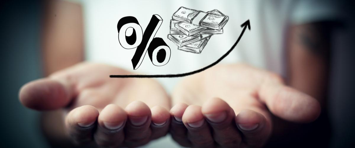 Percentageteken en geld zwevend in handen, met een pijl omhoog