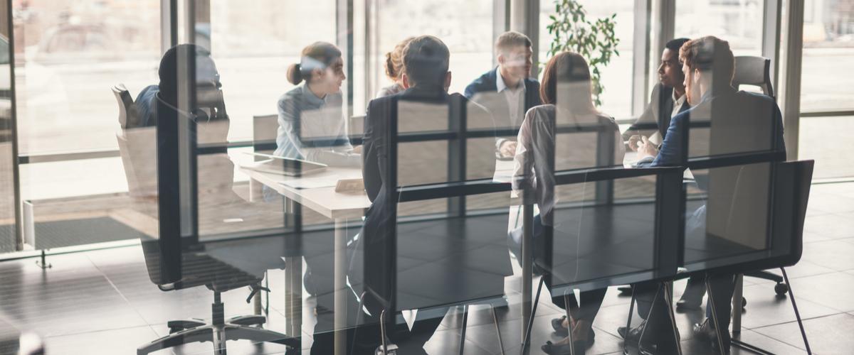 Vergadering met 6 mensen aan een tafel