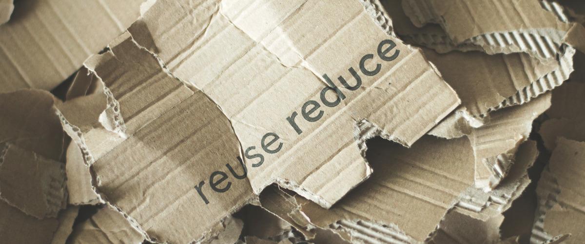 Gescheurd karton met de woorden reuse reduce erop