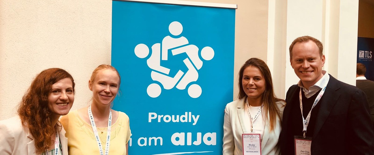 Nicky de Groot and three other boardmembers standing next to a blue AIJA congress flag