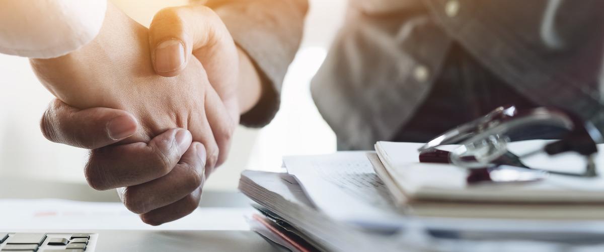 Twee handen die elkaar schudden bij het sluiten van een deal