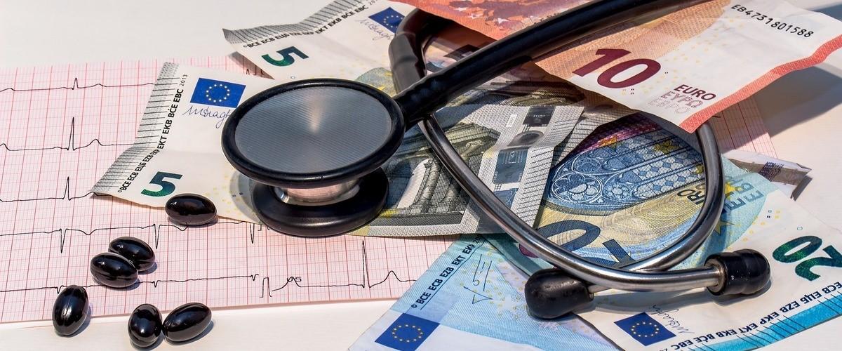 Stethoscoop, medicijnen en bankbiljetten op een stapel